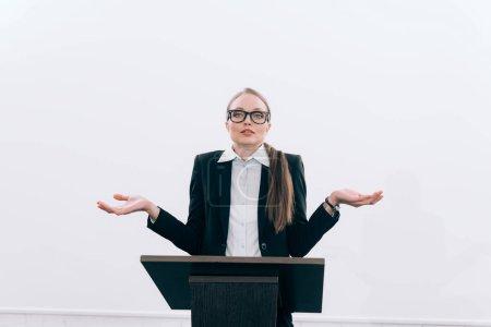 Photo pour Chargé de cours attractif debout à la tribune de podium et montrant le geste haussement d'épaules au cours du séminaire à la salle de conférence - image libre de droit