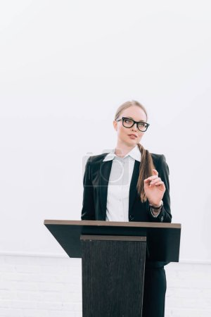 Photo for Beautiful lecturer standing at podium tribune and gesturing during seminar in conference hall - Royalty Free Image