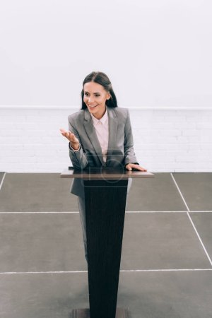 Photo for High angle view of attractive smiling lecturer gesturing at podium tribune during seminar in conference hall - Royalty Free Image