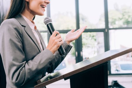 Photo for Cropped image of smiling lecturer talking into microphone and gesturing at podium tribune during seminar in conference hall - Royalty Free Image