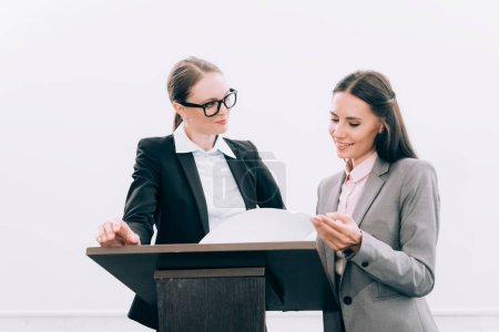 beautiful assistant showing documents to attractive speaker during seminar in conference hall