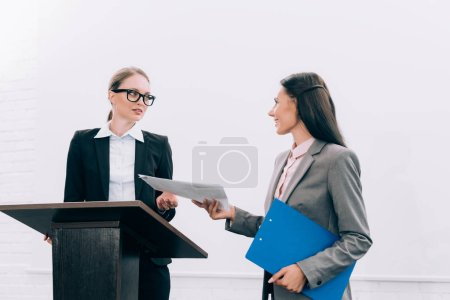 beautiful assistant giving documents to attractive speaker during seminar in conference hall