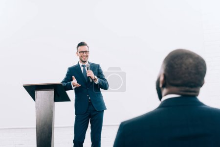 smiling caucasian lecturer talking to african american listener during seminar in conference hall