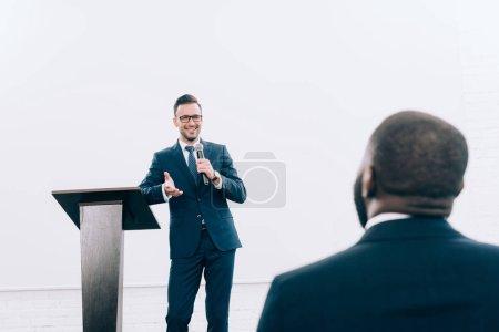 Foto de Sonriente el profesor caucásico hablando al oyente americano africano durante seminario en sala de conferencias - Imagen libre de derechos
