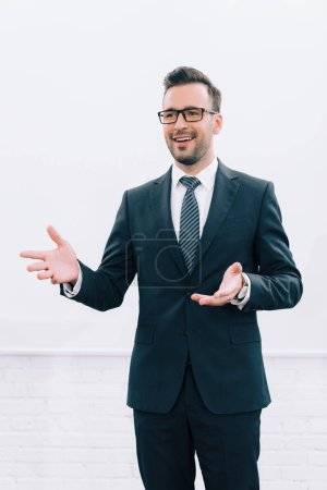 smiling handsome speaker in glasses talking and gesturing during seminar in conference hall
