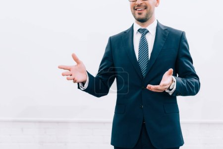 cropped image of smiling speaker talking and gesturing during seminar in conference hall