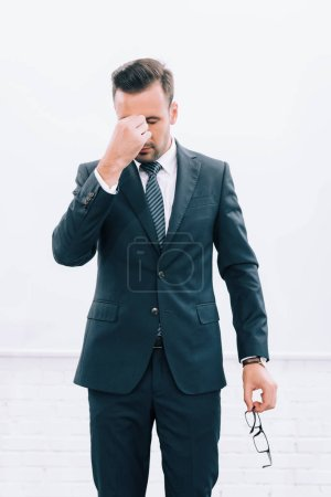 handsome tired speaker touching nose bridge during seminar in conference hall