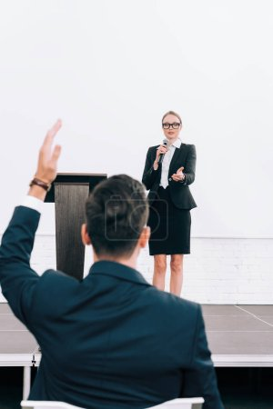 selective focus of attractive speaker talking into microphone during seminar in conference hall, participant raising hand