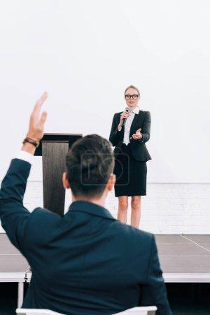 Foto de Enfoque selectivo del atractivo altavoz hablar por micrófono durante seminario en sala de conferencias, participante mano - Imagen libre de derechos