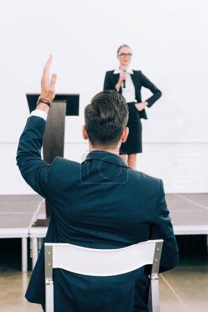 Photo pour Haut-parleur attrayant parler dans microphone au cours du séminaire dans la salle de conférence, participant élever main - image libre de droit