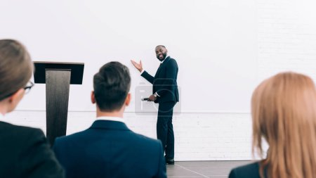 smiling handsome african american speaker talking during seminar in conference hall and pointing on screen