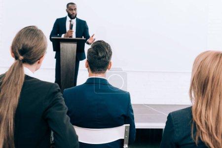Foto de Altavoz americano africano guapo hablar delante de la sala de audiencia - Imagen libre de derechos
