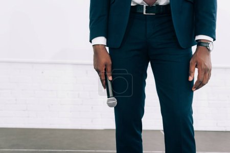 cropped image of african american businessman holding microphone during seminar in conference hall