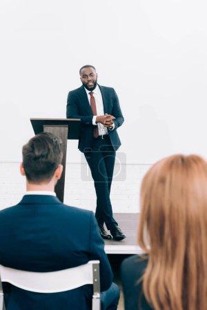 Photo pour Beau Président afro-américain s'appuyant sur la tribune du podium au cours du séminaire à la salle de conférence - image libre de droit