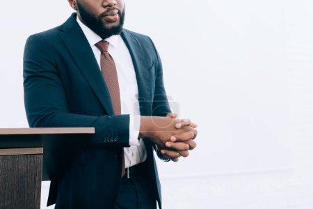 Photo pour Image recadrée d'un homme d'affaires afro-américain penché sur le podium tribune lors d'un séminaire dans une salle de conférence - image libre de droit