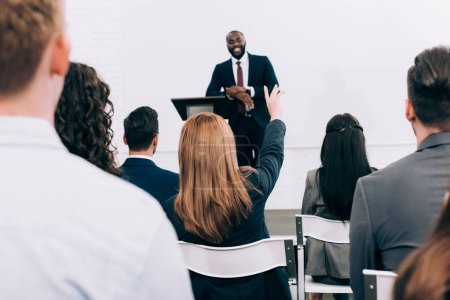 Photo for African american lecturer talking to audience during seminar in conference hall, participant raising hand - Royalty Free Image