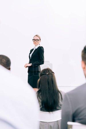 Photo pour Mise au point sélective de chargé de cours attractif regardant l'auditoire au cours du séminaire à la salle de conférence - image libre de droit