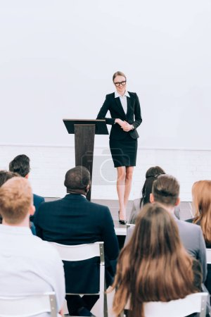 smiling attractive lecturer looking at multiethnic audience during seminar in conference hall