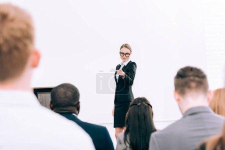 Foto de Atractivo profesor señalando audiencia multicultural durante seminario en sala de conferencias - Imagen libre de derechos
