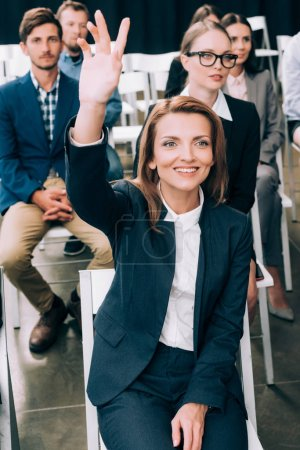 smiling businesswoman with hand up want to ask question during business seminar in conference hall