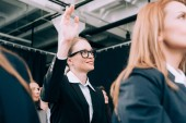 smiling businesswoman in eyeglasses with hand up want to ask question during business seminar in conference hall
