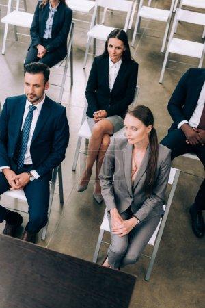 Foto de Vista de ángulo alto de empresarios multirraciales escuchando a la profesora durante el seminario de negocios en la sala de conferencias - Imagen libre de derechos