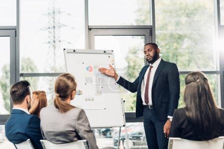 Photo pour Homme d'affaires afro-américain pointant vers le tableau blanc lors d'un séminaire d'affaires dans la salle de conférence - image libre de droit