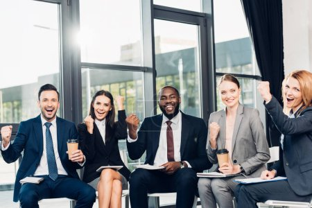 successful multiracial businesspeople sitting on chairs in conference hall