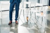 """Постер, картина, фотообои """"частичный вид бизнесмена, стоя на пустые стулья в конференц-зале"""""""