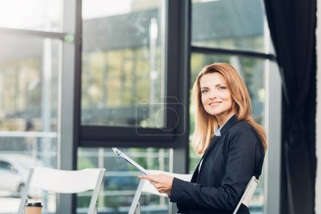 side view of businesswoman with notepad waiting for lecture in conference hall