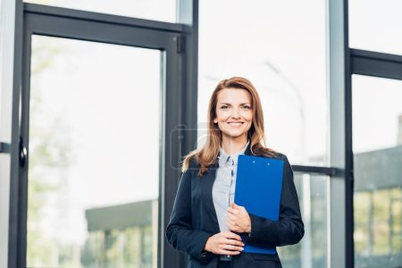 portrait of smiling businesswoman with notepad in conference hall