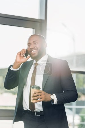 smiling african american businessman with coffee to go talking on smartphone in conference hall