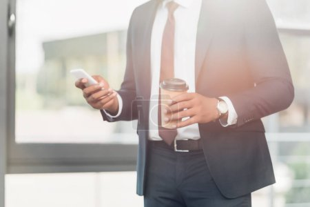 partial view of african american businessman with coffee to go using smartphone in conference hall
