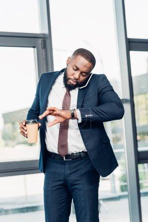 Photo pour Homme d'affaires africain-américain avec café pour aller vérifier le temps tout en ayant la conversation sur smartphone dans la salle de conférence - image libre de droit