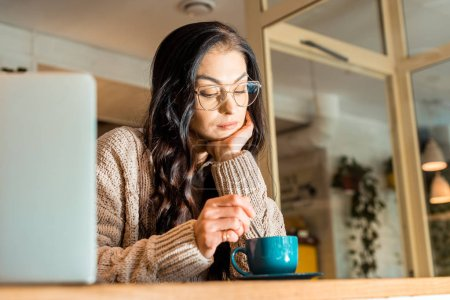attractive pensive woman in glasses sitting in cafe with cup of tea