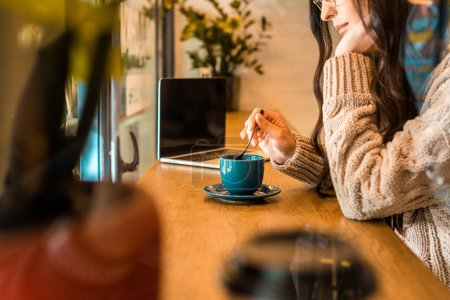cropped image of woman in glasses sitting in cafe with cup of tea