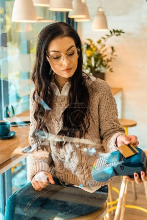 beautiful woman paying with credit card by contactless payment in cafe