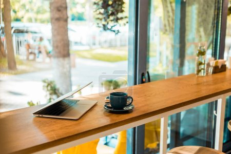 Photo pour Ordinateur portable et tasse de café sur comptoir de café en bois - image libre de droit