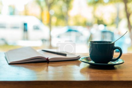 cup of coffee and open notebook with pen on wooden table in cafe
