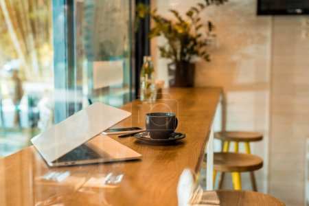 laptop, smartphone, notebook and cup of coffee on wooden cafe counter