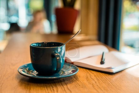 cup of coffee with spoon and open notebook with pen on wooden tabletop in cafe