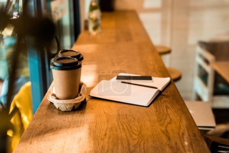 two disposable coffee cups, open notebook with pen on cafe counter
