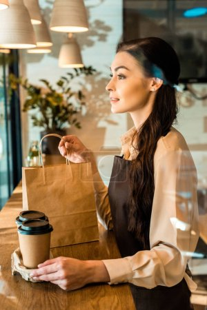 side view of beautiful waitress in apron holding disposable coffee cups and paper bag in cafe