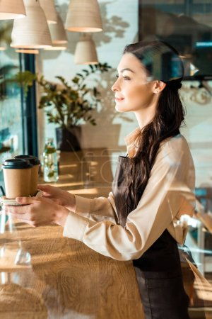 side view of beautiful waitress in apron holding disposable coffee cups in cafe