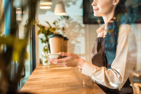 cropped image of waitress in apron holding coffee in paper cups in cafe