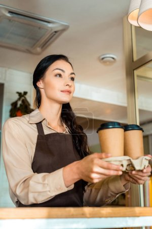low angle view of brunette waitress holding coffee in paper cups in cafe
