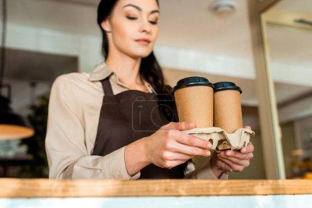 Photo pour Vue à angle bas de serveuse attrayante dans tablier tenant café dans des tasses en papier dans le café - image libre de droit