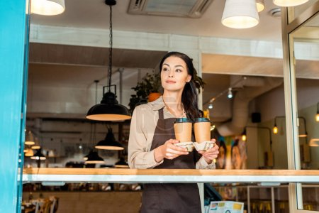 beautiful waitress in apron holding coffee in paper cups in cafe and looking away