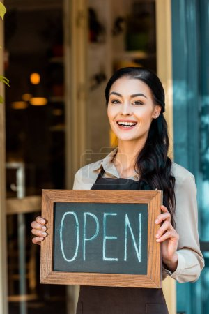 Photo for Happy beautiful cafe owner in apron holding open signboard near cafe and looking at camera - Royalty Free Image