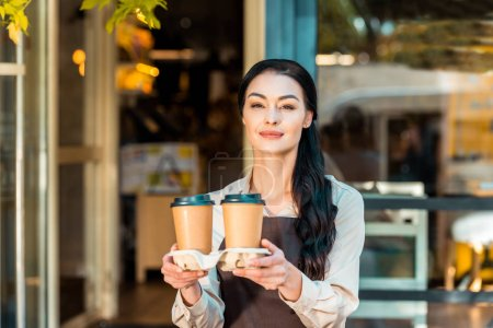 beautiful waitress in apron holding two coffee in paper cups near cafe